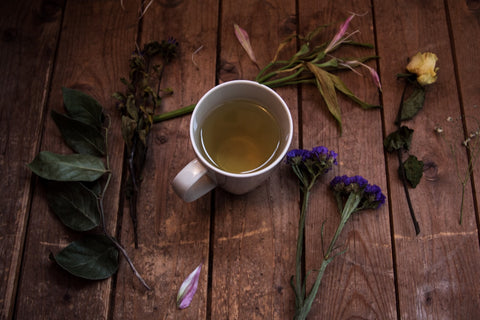 cup of tea surrounded by flowers and twigs