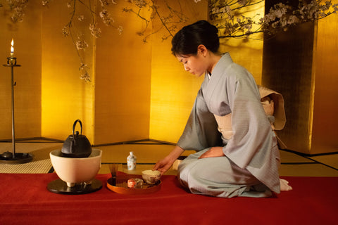 woman sitting inside room doing tea ceremony