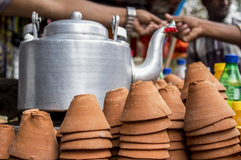 a kettle and small clay cups for chai tea