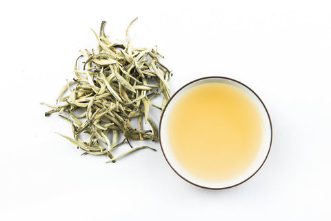 white tea in saucers beside a heap of white tea leaves