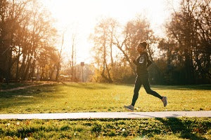 A woman running in the park, participating in virtual races with medals in the US