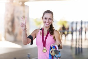 An athlete showing off her swag from virtual runs with medals in the US