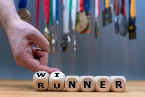 A hand changing letter blocks from runner to winner, with medals from a virtual run in the background