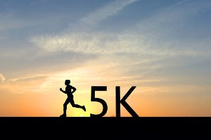 """The silhouette of a runner with the words """"5K"""" behind them"""