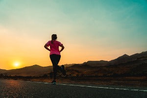 A woman running a virtual half marathon at the end of the day