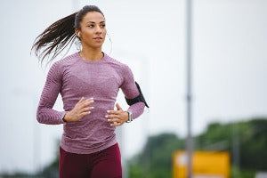 A woman running outside, participating in a virtual run in the US