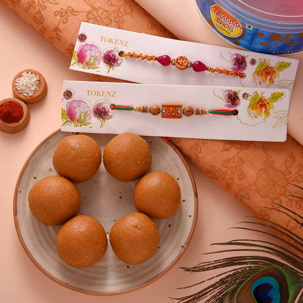 Traditional Set Of 2 Om & Ganesha Rakhis With Besan Laddoo