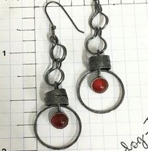 "Load image into Gallery viewer, Made with patinated Sterling Silver and Argentium™ these earrings will make you want to dance!  Carnelian contains energy and more than a bit of feistiness so put on those dancing shoes and get moving!  The 6mm Carnelian is set in a serrated bezel.    20g Argentium™ ear wire  3"" L x 15/16""W"