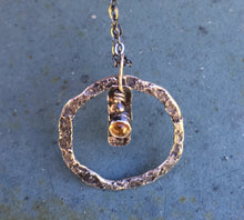 "Load image into Gallery viewer, Citrine is said to harness the energy of the sun bringing light to all areas of life.  The joyful color of the 3mm stone will help to brighten the winter days.  Textured and patinated Sterling Silver emphasize the Citrine.  Chain:  18"" Patinated Sterling Silver with Spring Clasp  Charm:  3/4"" Diameter Made with Sterling Silver and Argentium™"