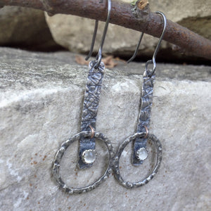 "A stone for wishing and hope, Moonstone offers help with understanding through intuition.  These simple, hand-textured Sterling Silver earrings feature a 4mm bezel-set Moonstone.     20 gauge patinated Argentium™ ear wires  Total Length:  1 3/4"" from the top of the ear wire to the bottom of the charm.  Charm Size:    1 3/8"" long x 1/4"" wide"