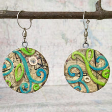 "Load image into Gallery viewer, United is often two sides of the same coin.  Many paper layers created a pair of earrings that are the same but different.  No matter what ""spin"" is put on it, they go together."