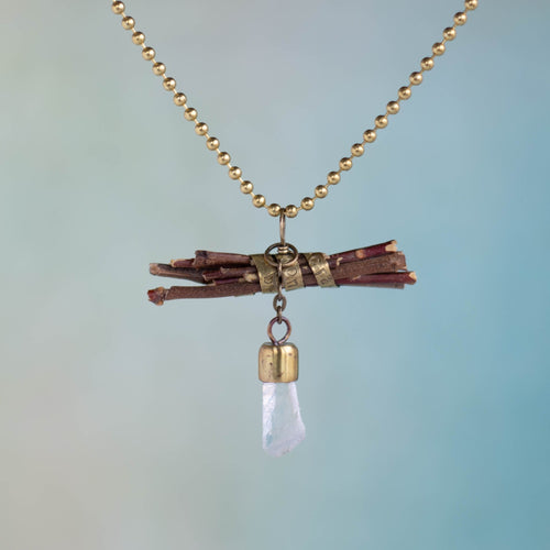 """Wisdom begins in wonder"" (Socrates) is stamped on a brass band that wraps around a bundle of sticks on this handmade necklace.  Flashing light as it moves, a Quartz crystal dangles on a small, brass chain."