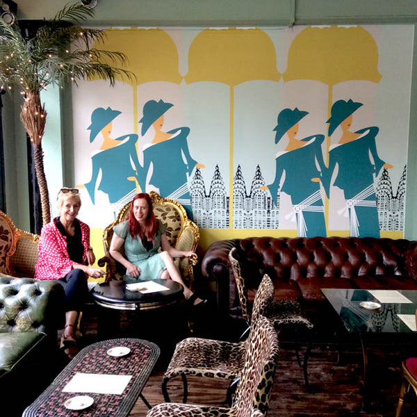 Owners of Metrodeco in front of High Society Art Deco Mural by ATADesigns