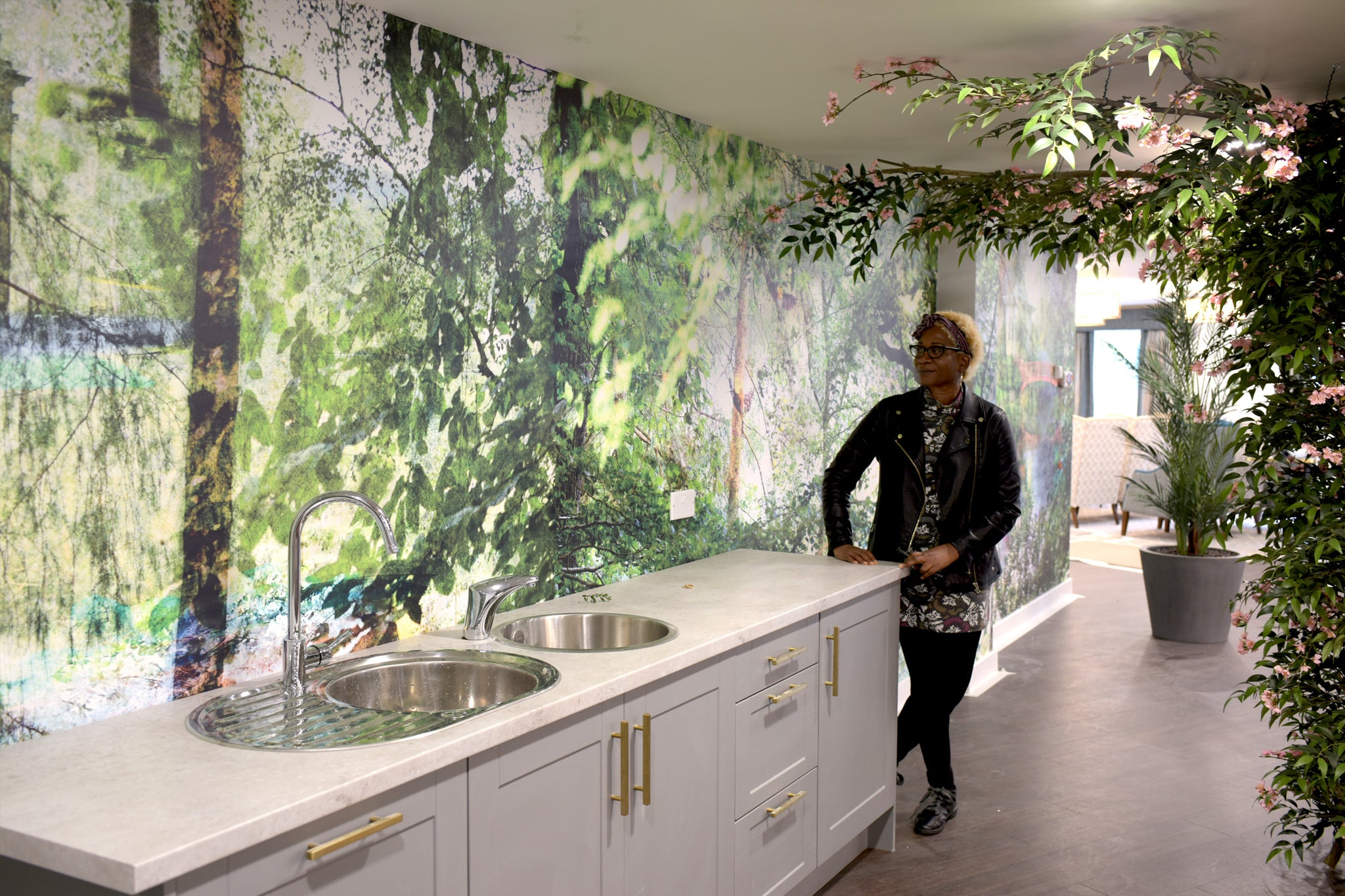ATADesigns infront of her bespoke nature wall mural design installed at the Dora Rose Care Home, Staffordshire