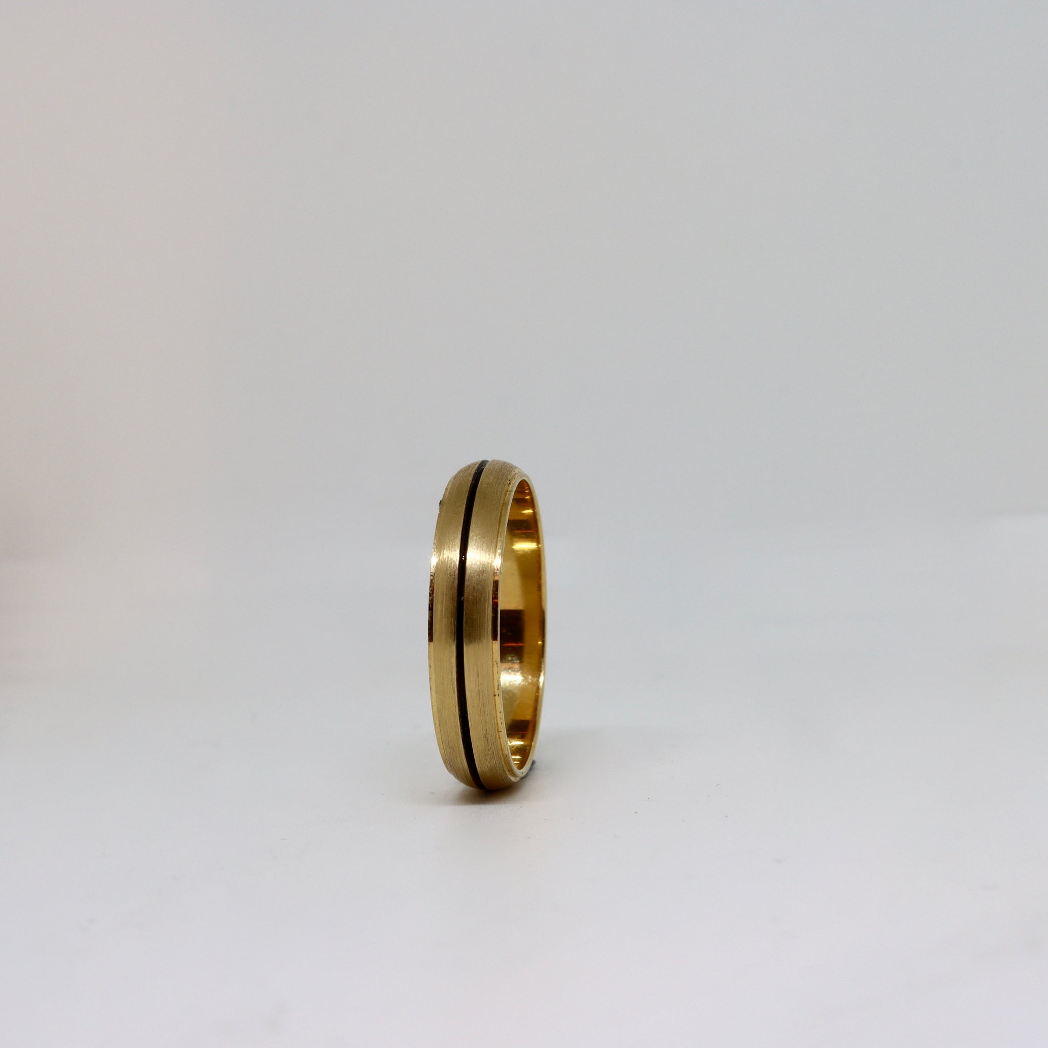 Yellow brushed finished band with a black etched line
