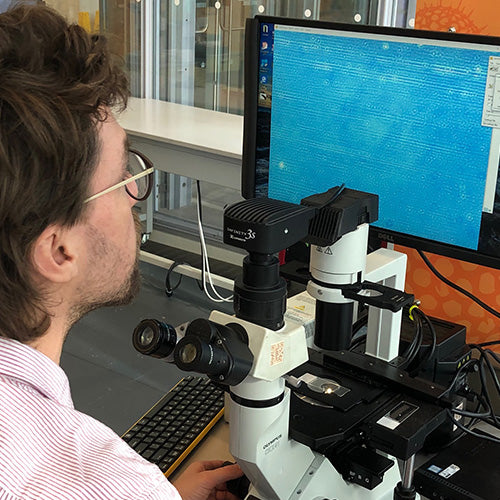 Scientist examining holy water under an electron microscope and seeing it displayed on a computer monitor.