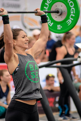 Strong woman overhead pressing at crossfit competition
