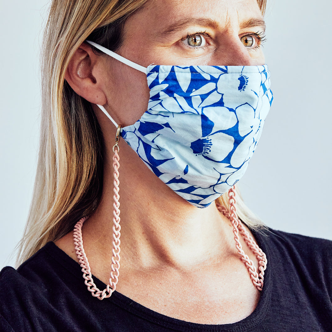 Woman wearing light pink mask chain with a blue floral mask