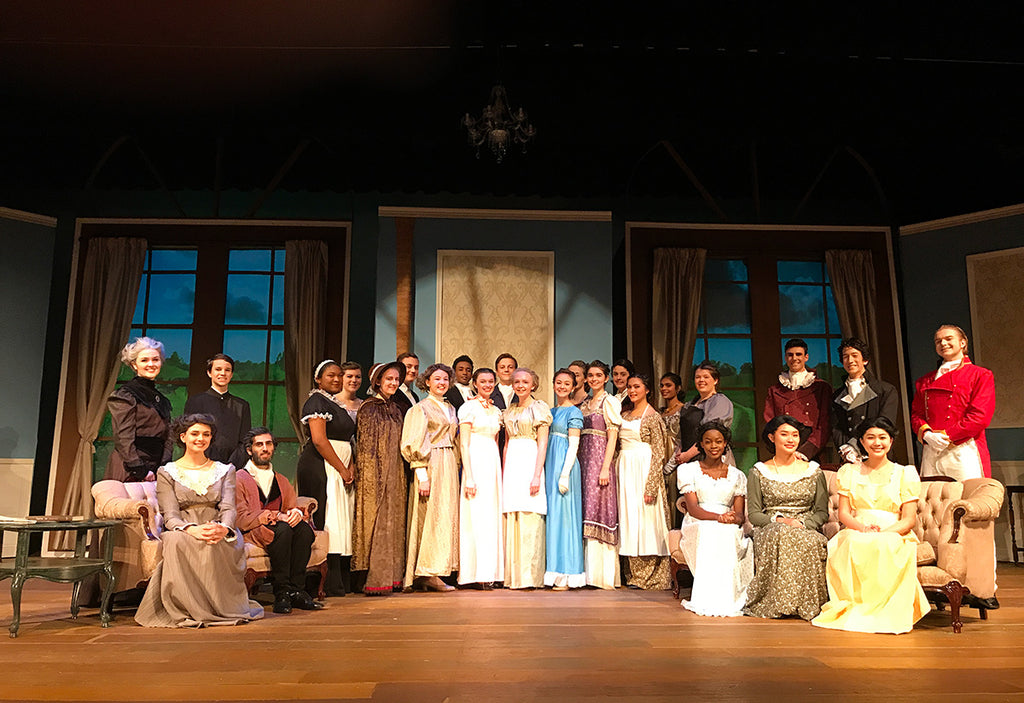 Pride and Prejudice cast standing on stage with digital projections in the windows