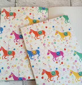 Notebook with carousel horses illustration