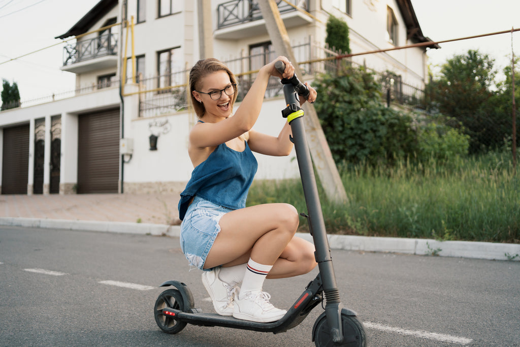 Millennial woman riding an electric scooter in the street