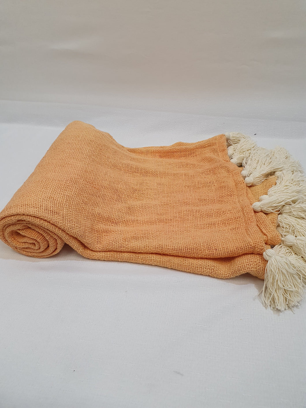 Soft orange throw with white tassel ends