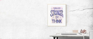 "MarcoLooks print framed on a marble looking wall. Print reads ""You Are Stronger Than You Think"" in shades of peach and purple. Below is a desktop with a laptop. The frame is a light wood. The overall image is relaxing and aspirational"