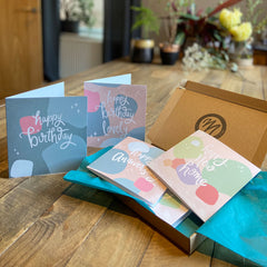 MarcoLooks Greetings Cards Club. Cards for any occasion sent straight to your home. Photo shows a selection of cards, on a beautiful wooden table. The cards sit in a small brown box with teal tissue paper