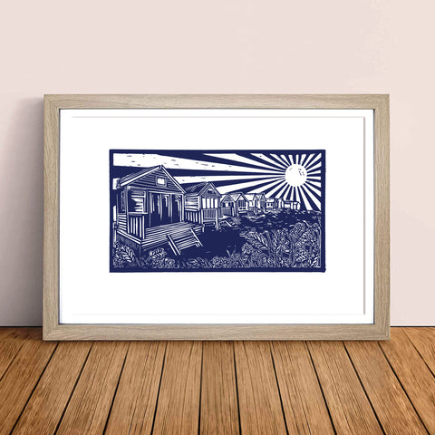 MarcoLooks framed print of the Beach Huts at Mudeford, printed in blue ink. Taken originally from a lino cut print. The print is pictured in a wooden frame, resting against a pale peach wall, on a oak floor board.