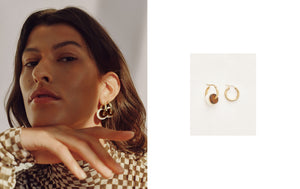 A portrait of a model in an expressive pose wearing the golden AVA earrings with two different acetate rings. The two acetate rings have different colors.