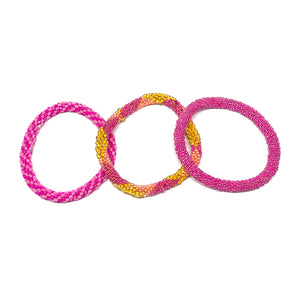 "These ""Pink Punch Roll Ons"" come as a set of three.  They are handmade with love by women artisans in Nepal, using high quality glass beads and hand-dyed cotton thread. These bracelets will expand over your hand to fit most wrist.   The purchase of these bracelets empowers female artisans through fair trade. Your purchase provides women with fair income + benefits in a safe and healthy work environment. Aid Through Trade empowers women by creating opportunity through beautifully designed jewelry."