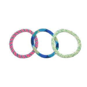 "These ""Aloha Roll Ons"" come as a set of three.  They are handmade with love by women artisans in Nepal, using high quality glass beads and hand-dyed cotton thread. These bracelets will expand over your hand to fit most wrist.   The purchase of these bracelets empowers female artisans through fair trade. Your purchase provides women with fair income + benefits in a safe and healthy work environment. Aid Through Trade empowers women by creating opportunity through beautifully designed jewelry."