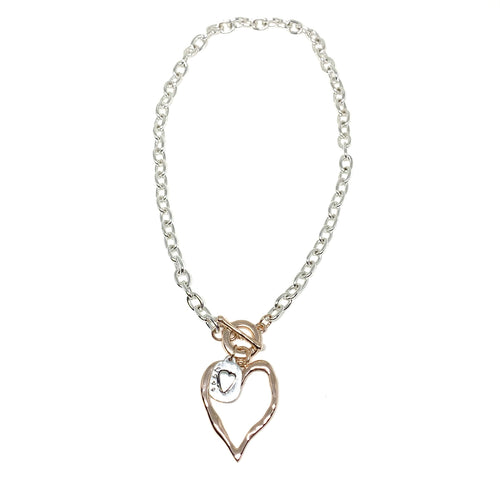 "Discover eye-catching, straight-off-the-runway inspired pieces. One statement piece, infinite possibilities…  This short necklace has a rose gold heart with a silver love pendant.   Merx Modern is exclusively designed and handmade in Canada.  This necklace length is 20"" + toggle closure"