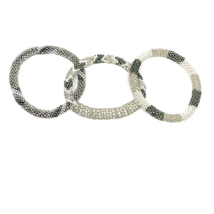 "These ""Silvery Moon Roll Ons"" come as a set of three.  They are handmade with love by women artisans in Nepal, using high quality glass beads and hand-dyed cotton thread. These bracelets will expand over your hand to fit most wrist.   The purchase of these bracelets empowers female artisans through fair trade. Your purchase provides women with fair income + benefits in a safe and healthy work environment. Aid Through Trade empowers women by creating opportunity through beautifully designed jewelry."