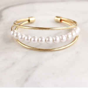 Elaine Pearl Bracelet features three thin, smooth bands, with a row of pearls in the middle. Beautiful and simple, this bracelet is the perfect feminine complement.  14k Gold plated on Brass, Synthetic Pearls Diameter: 2.5 inches