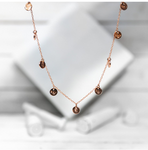 A classic multi-charm design that sits slightly looser than a choker, and is adjustable to fit various neck sizes. Each charm is stamped on both sides with B&U markings.  This necklace is rose gold plated stainless steel with a lobster clasp.   Length: 18""