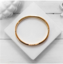 Load image into Gallery viewer, The Unity Bangle is modelled after the end of a bullet casing, featuring a similar groove and stamped markings around the front and back surfaces - a subtle, yet meaningful reference to Brass & Unity's story.   This bangle is 24K gold plated stainless steel with an integrated snap feature.    Size: SM/MD