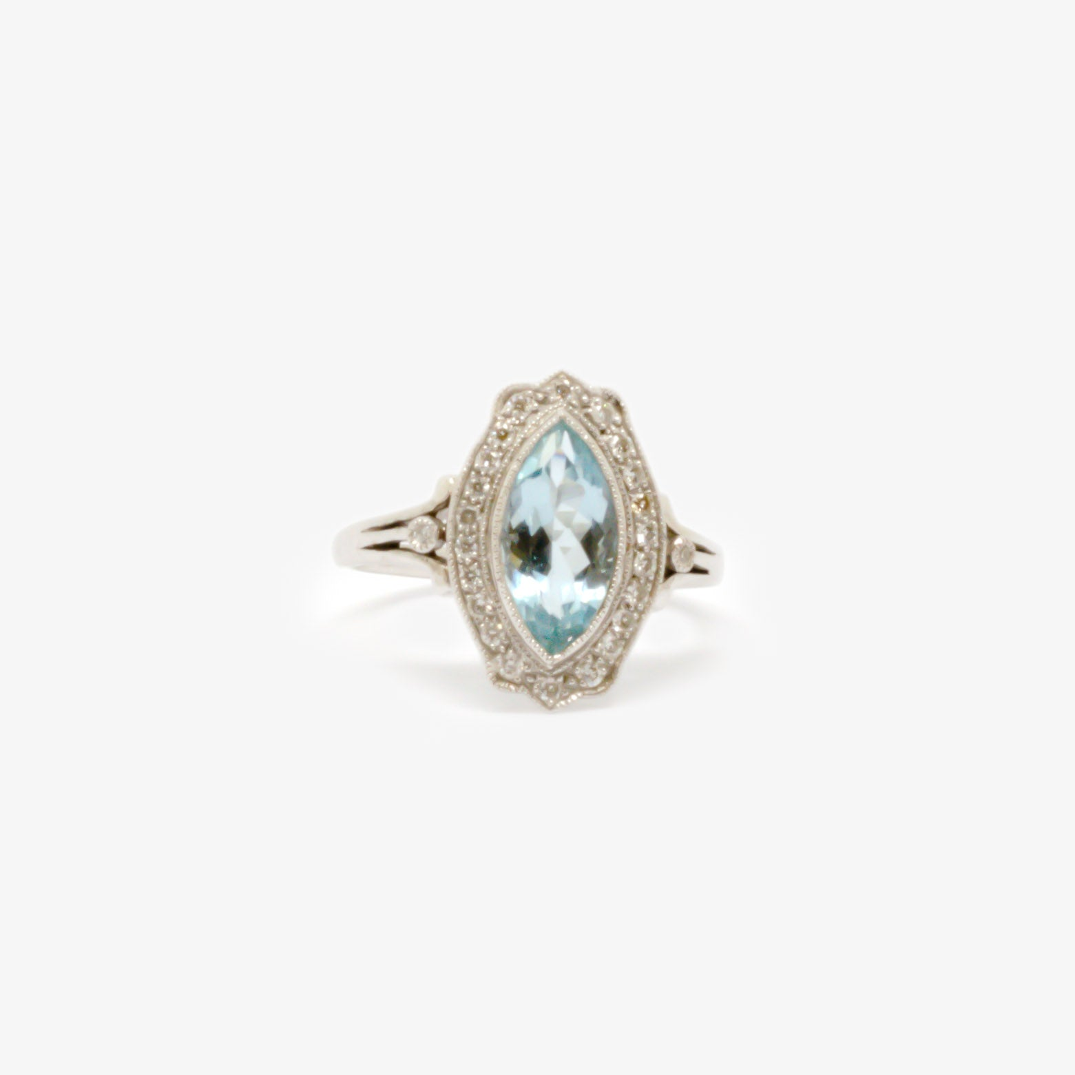 Ring in white gold with an aquamarine in the centre surrounded by diamonds and two diamonds on the either side.