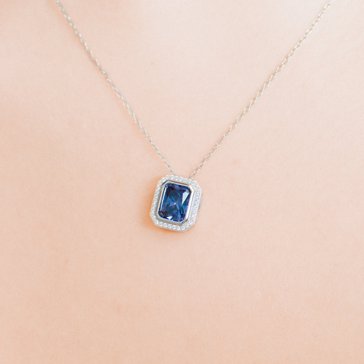 Lifestyle picture of the dark blue rectangle cubic zirconia pendant necklace on a person.