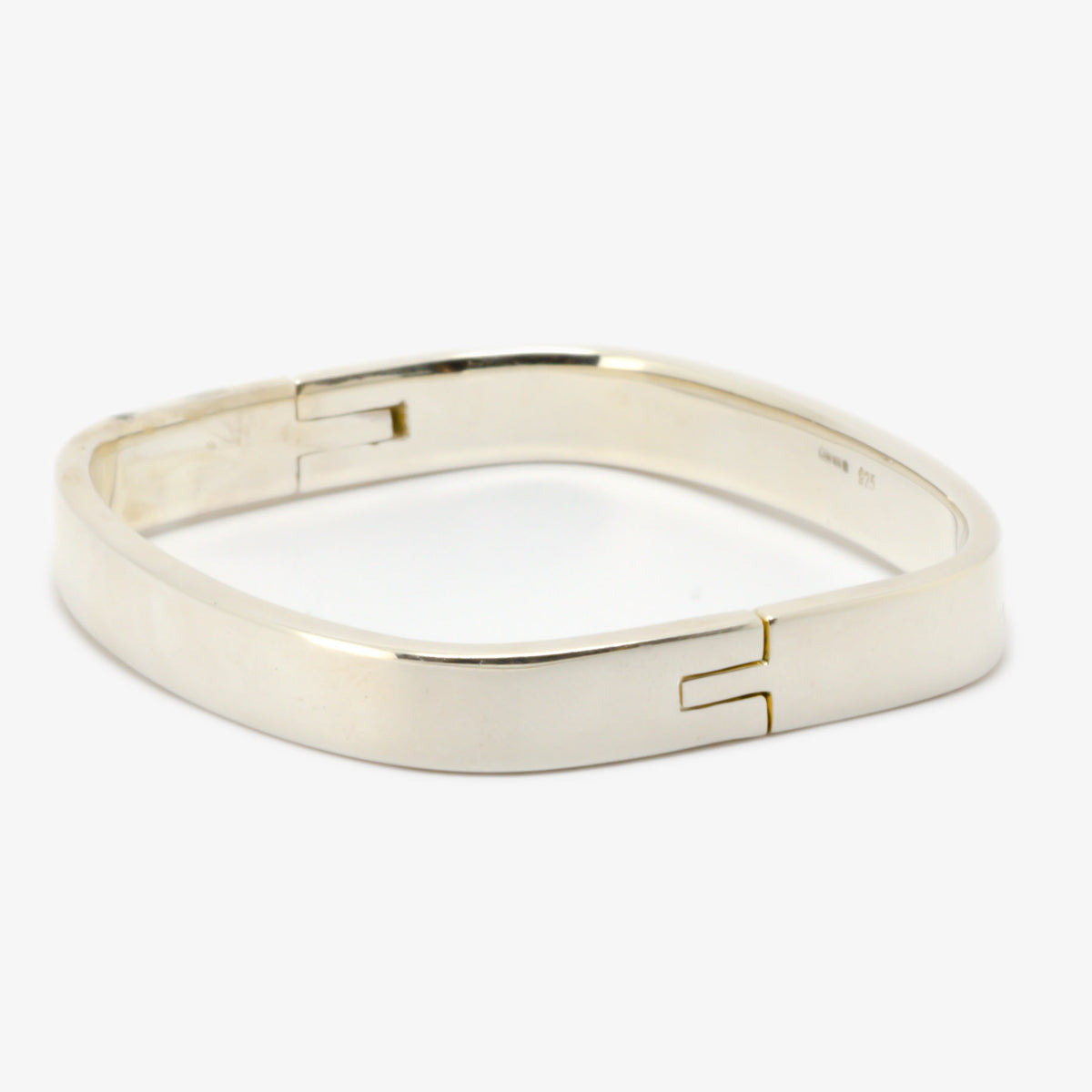 Picture of a bangle in silver shaped like a 'TV' and is hinged on the side making it easy to put on and take off side view.