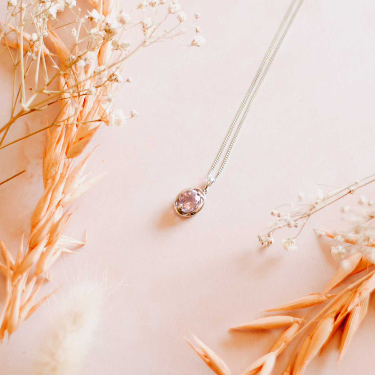 Picture of the silver oval amethyst pendant necklace on a pink background surrounded by dried flowers.