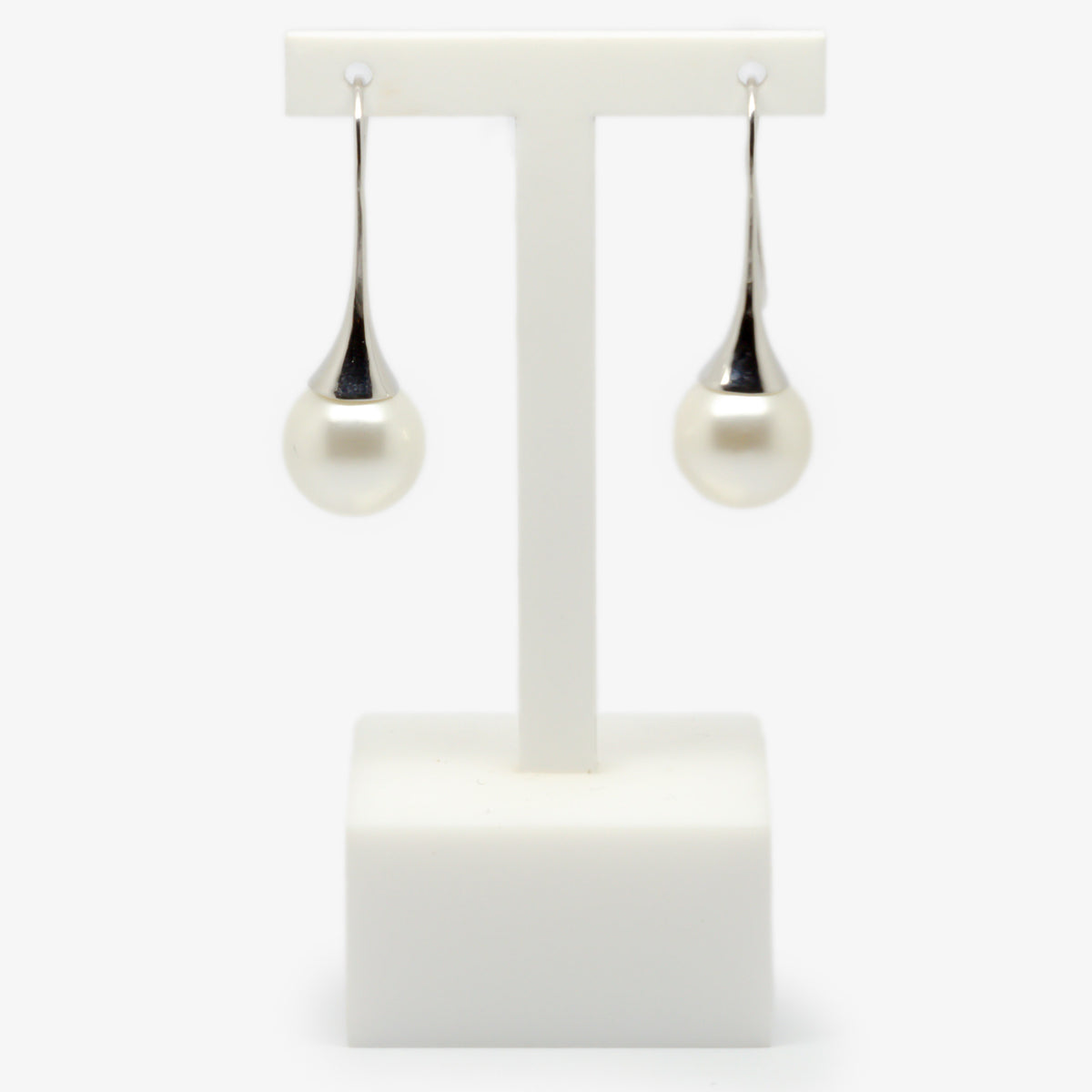 White shell pearl drop earrings on a earrings stand front view