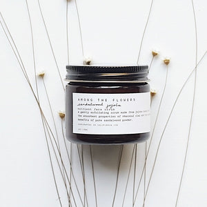 Sustainable facial scrub packaging next to flowers