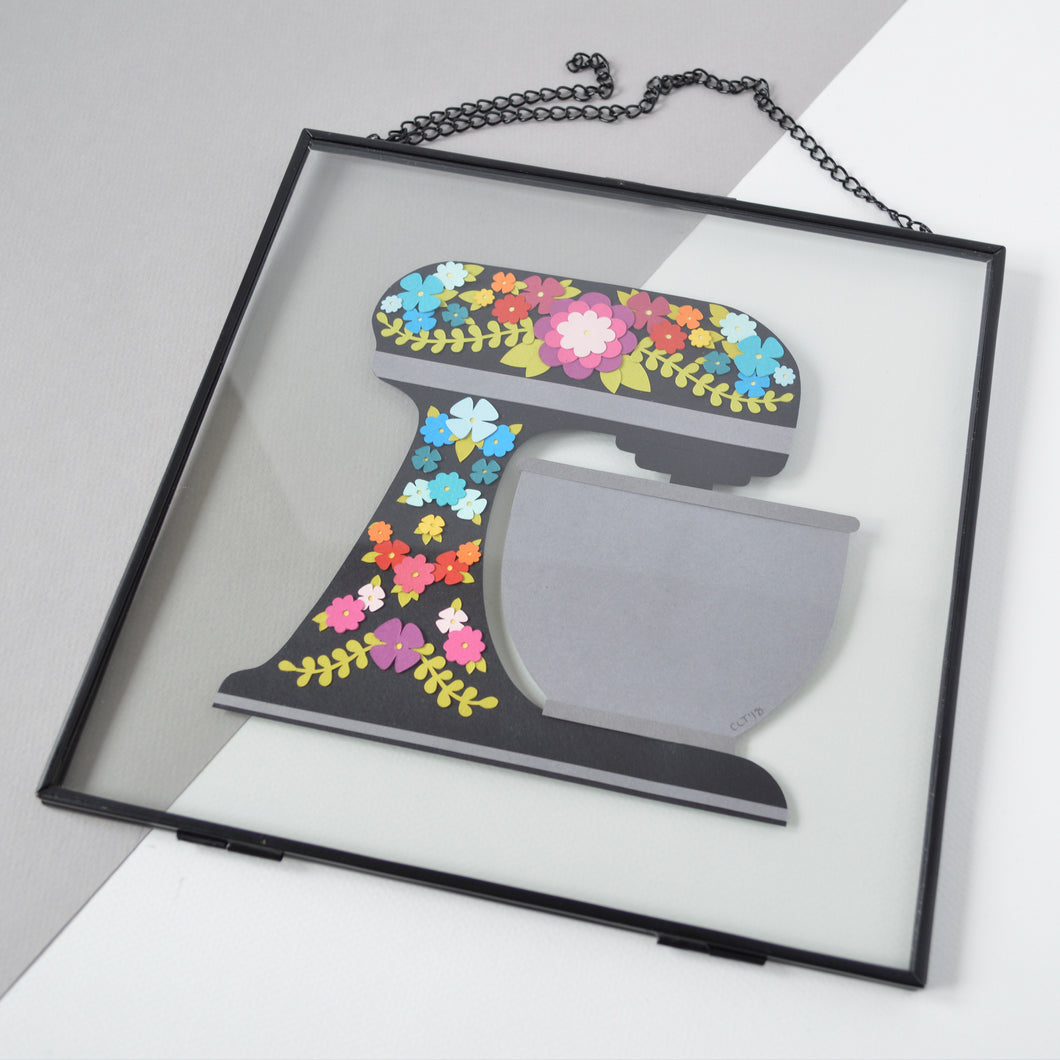 A handmade papercut of a black kitchen mixer decorated with flowers in rainbow colours in a black metal frame