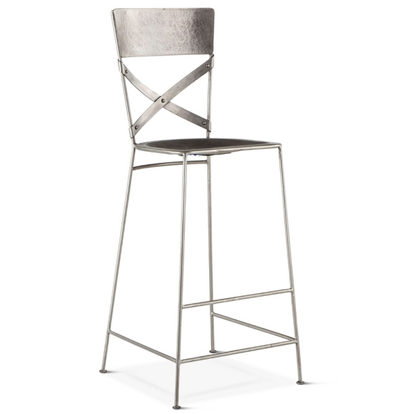 Slightly slanted front view reclaimed iron bar stool with hand hammered texturing in a nickel finish. Contoured seat, cross back with riveted joinery.