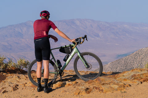Gravel and road bike rider overlooking views with frame bag by Lead Out!