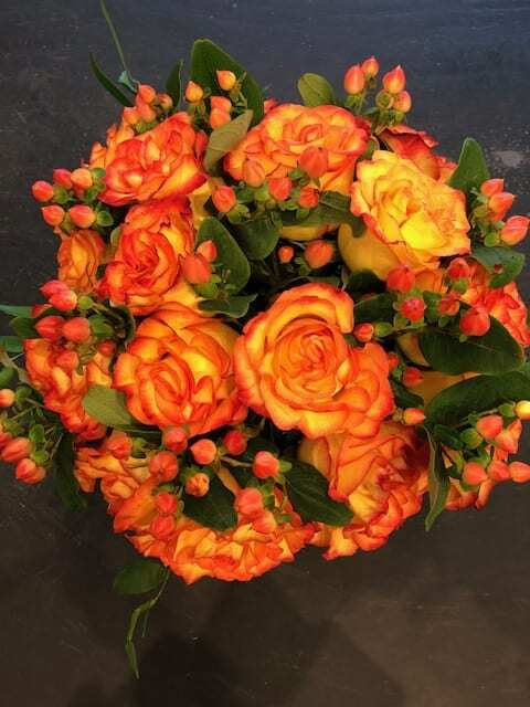 Rose arrangement with hypericum in square glass vase