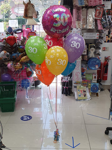 A bunch of six printed balloons, a pink 30th foil balloon and a weight