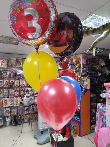 three brightly coloured latex helium balloons, one 3rd birthday and one Disney Cars foil balloon