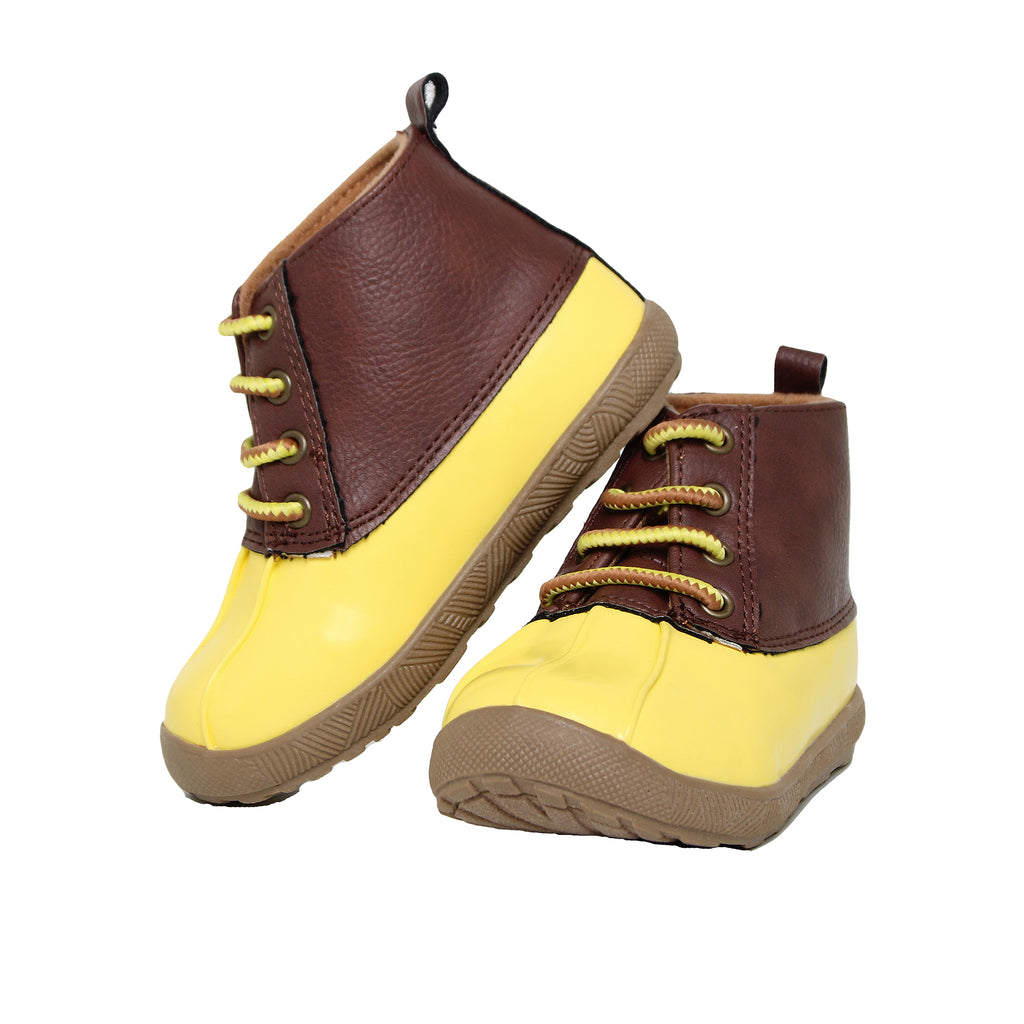 Angled view of baby toddler rainboots with patent leather shoe tops and bright yellow rubber water proof bottoms and soles